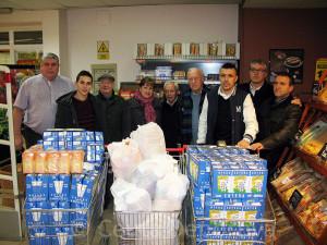 Directivos y jugadores del Ceutí, responsables de Cáritas y el gerente de Supersol, con las carros de alimentos donados